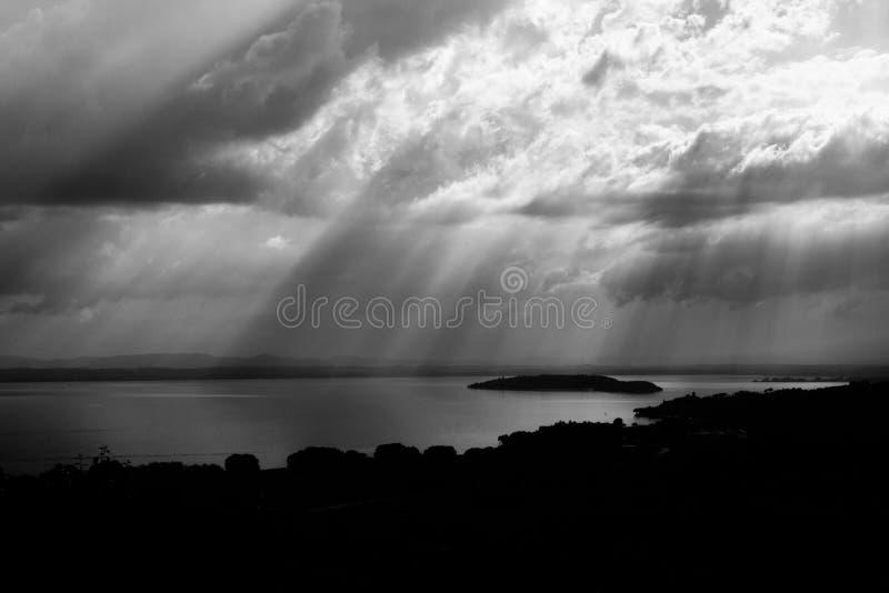 Sun irradia sair através das nuvens sobre uma ilha em um lago imagens de stock