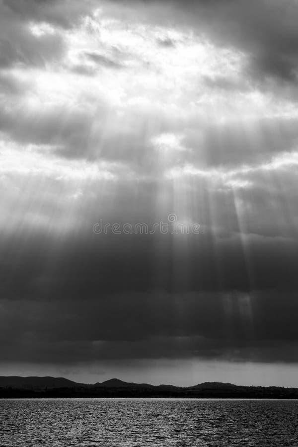 Sun irradia salir a través de las nubes sobre un lago fotografía de archivo libre de regalías