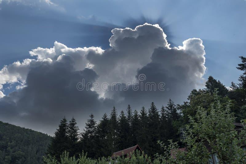 Sun irradia venir de debajo las nubes de tormenta oscuras sobre el bosque negro y los tejados de casas imagenes de archivo