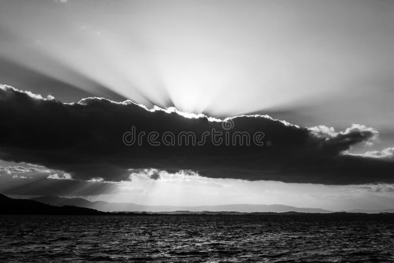 Sun irradia venir a través de algunas nubes sobre un lago fotos de archivo libres de regalías