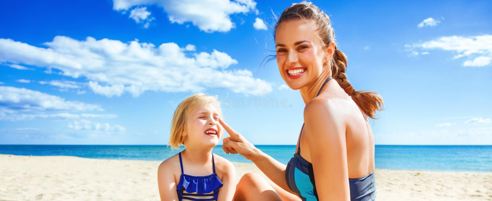 Happy young mother and daughter on beach applying sun block stock photo