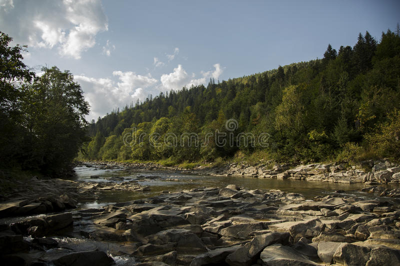 Sun, landscape, river and stones royalty free stock images