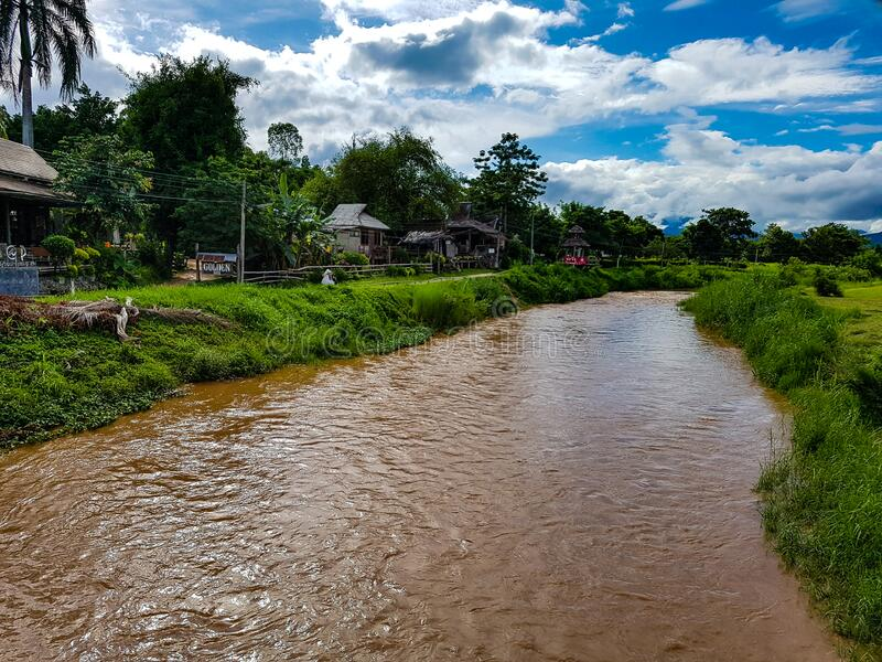 Sun light behind moving clouds blue sky over brown dirt river green grass palm tree house pai in north chiang mai. Thailand stock photography