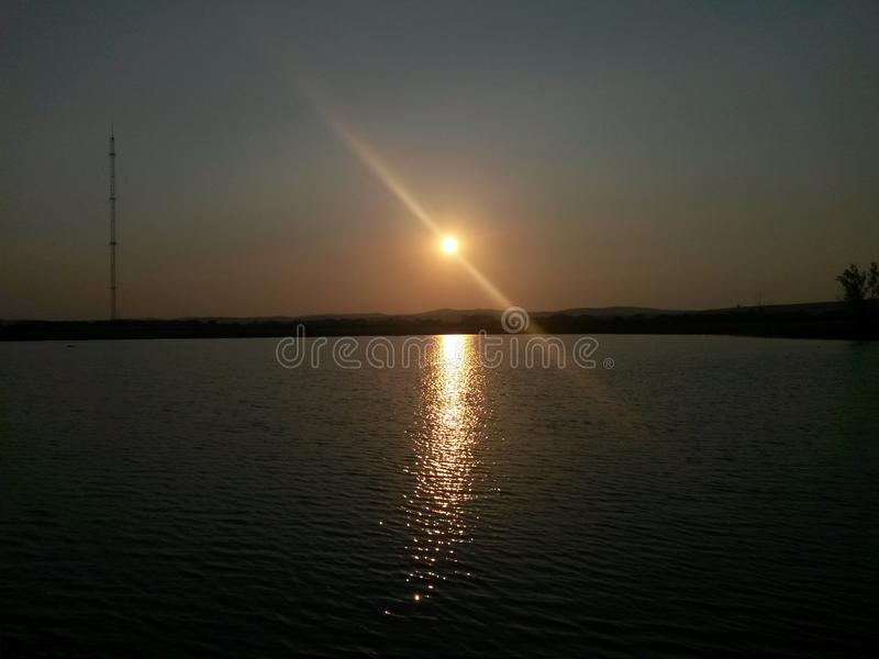 Sun with light effect over lake and radio transmitter on background. Image royalty free stock photography