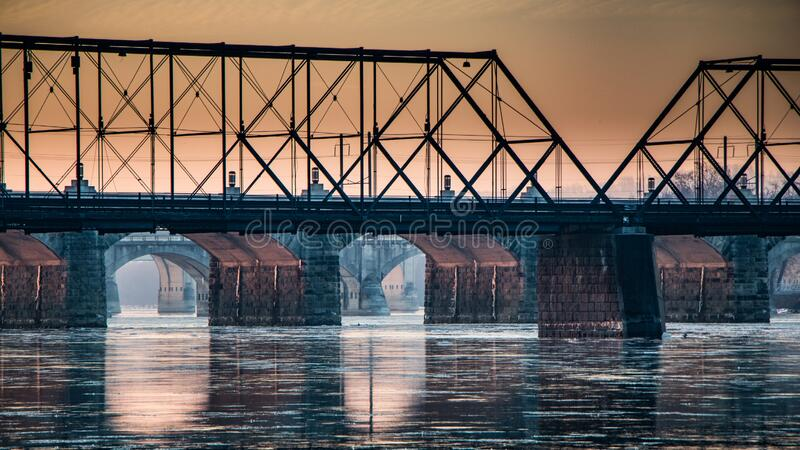 Sunrise through the arches of a series of bridges over the Susquehanna River in Harrisburg, PA. The sun lights up the underside of a series of bridges over the stock image