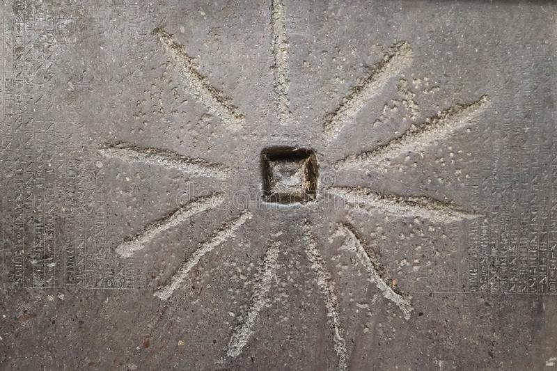 Sun-like design on ancient Egyptian building with faint hieroglyphs to the sides. A Sun-like design on ancient Egyptian building with faint hieroglyphs to the stock images