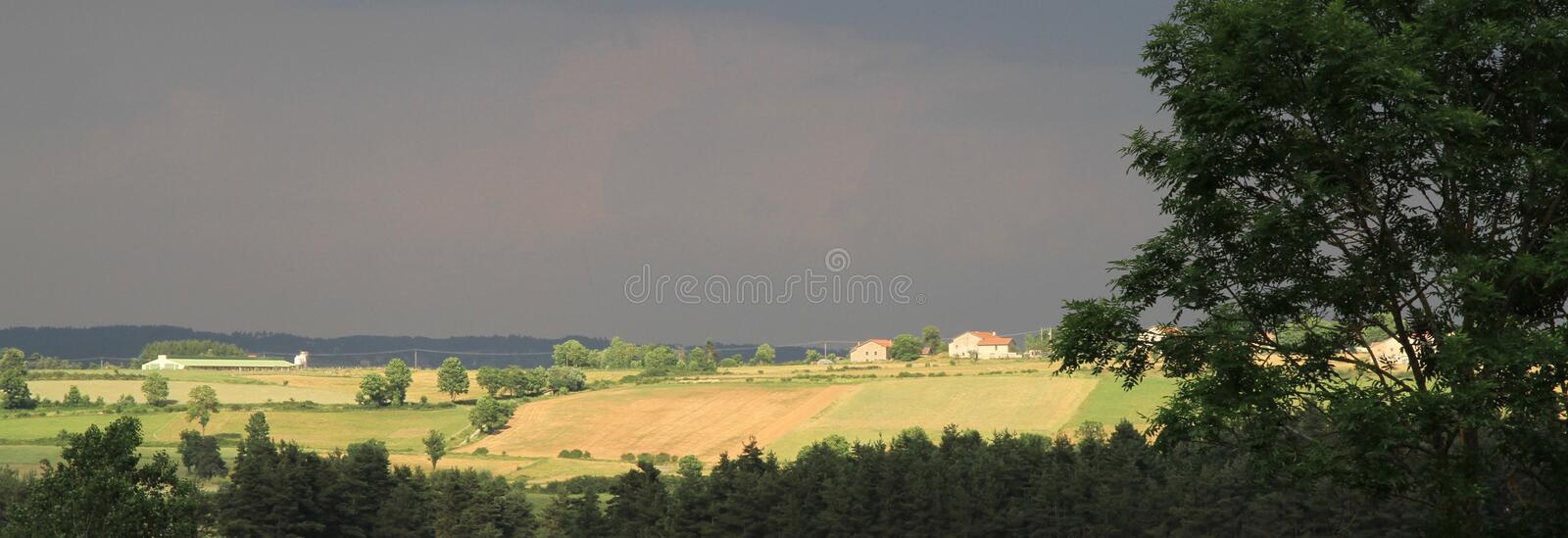 Sun lit fields after a storm in the Auvergne in France. A landscape image with foreground trees to sun lit fields and dark skies in the background royalty free stock images