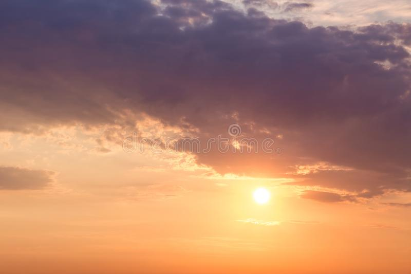 The sun looks like because of clouds in the evening. The sky at stock images