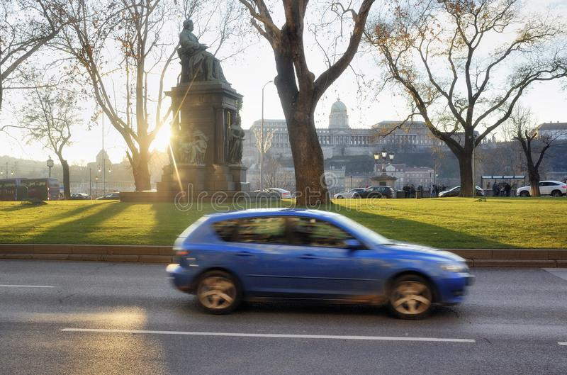 The sun looks from the monument of Deak Ferenc in Budapest. Buda castle on the background and blue car in motion on foreground royalty free stock photo