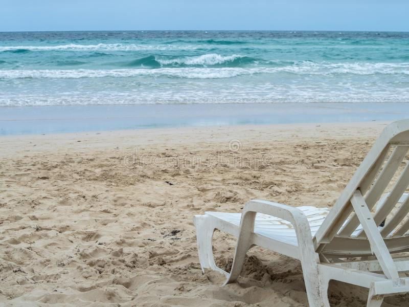Sun lounger on the beach with a stormy sky and waves royalty free stock photography