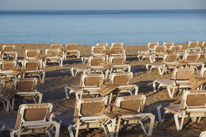 Sun loungers and closed umbrellas at a seaside resort , the calm and relaxed atmosphere of the summer holiday.  stock images
