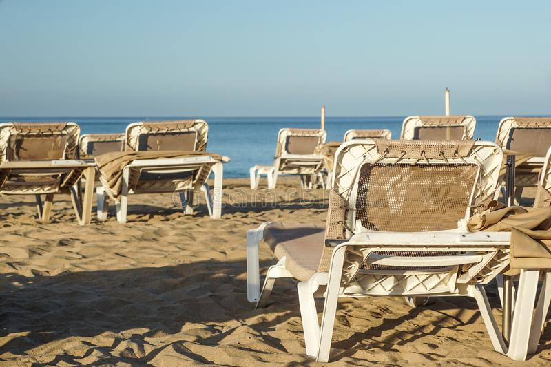 Sun loungers and closed umbrellas at a seaside resort , the calm and relaxed atmosphere of the summer holiday.  stock photos