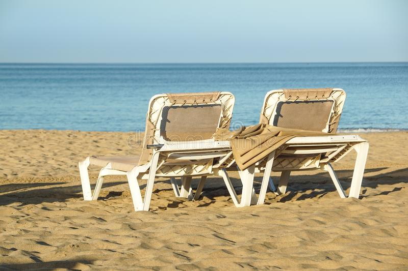 Sun loungers and closed umbrellas at a seaside resort , the calm and relaxed atmosphere of the summer holiday at sunset.  royalty free stock image