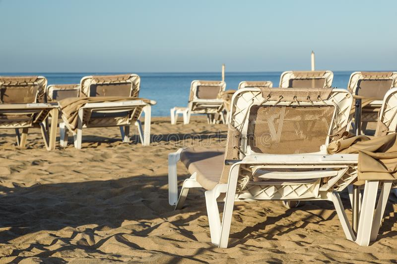 Sun loungers and closed umbrellas at a seaside resort , the calm and relaxed atmosphere of the summer holiday at sunset.  royalty free stock photos