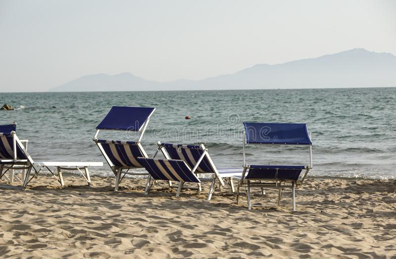 Sun loungers empty at seaside resort , the calm and relaxed atmosphere of the summer holiday at sunset.  royalty free stock images