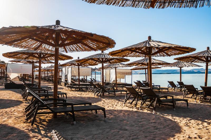 Sun loungers and parasols on the sandy beach stock photo