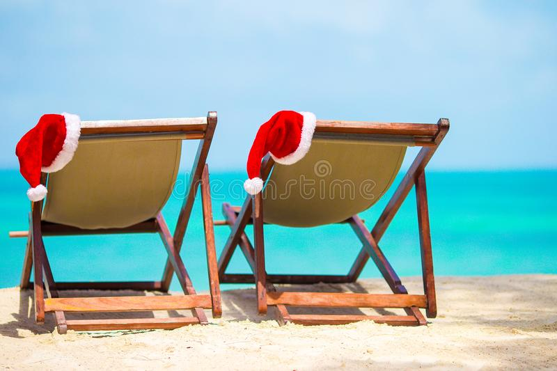 Sun loungers with Santa Hat at beautiful tropical beach with white sand and turquoise water. Perfect Christmas vacation. Santa Claus Hat on beach lounger with stock photography