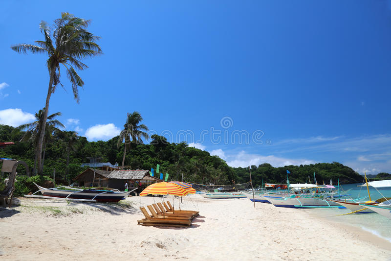 Sun lounges with umbrellas at Ilig Iligan Beach, Boracay Island, Philippines. Sun lounges and boats at Ilig-Iligan Beach, Boracay Island, Philippines royalty free stock photo