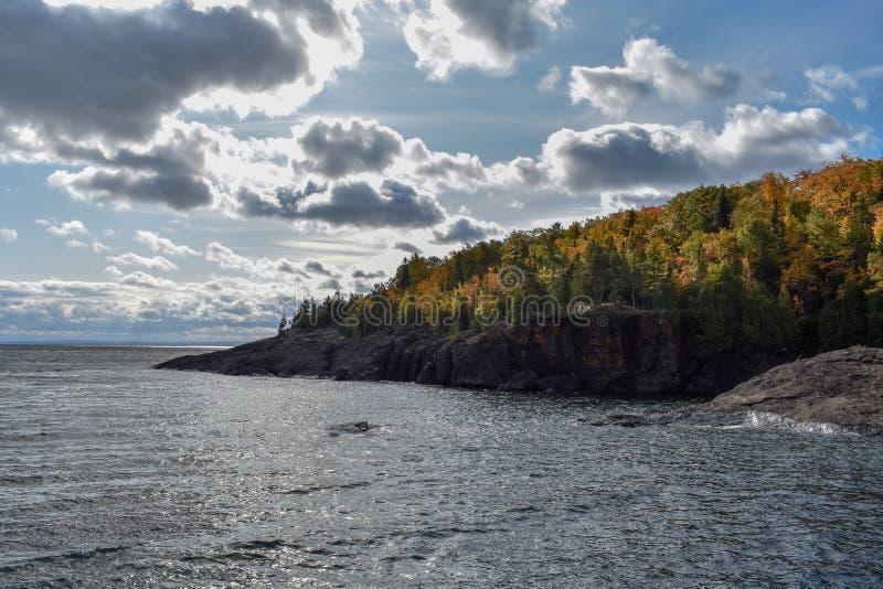Sun lyser på träd som ändrar färg längs sjöns superior kustlinje royaltyfri foto