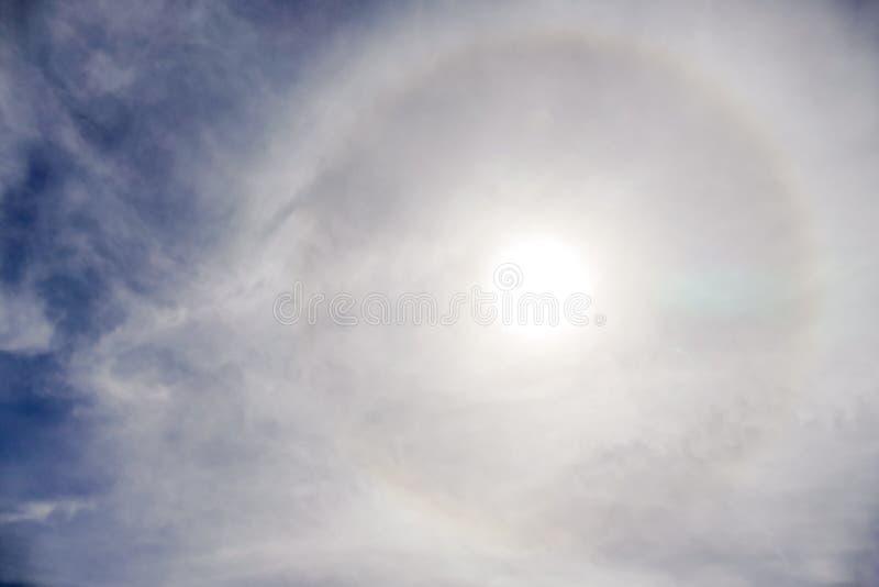 Sun mit dem Kreisregenbogensonnen-Haloauftreten wegen der Eiskristalle in der Atmosphäre, Sonnenhalohintergrund stockfotos