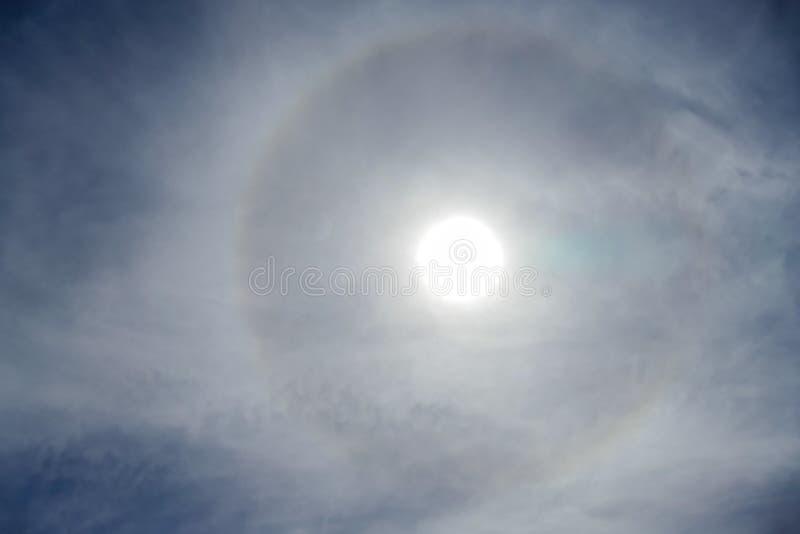 Sun mit dem Kreisregenbogensonnen-Haloauftreten wegen der Eiskristalle in der Atmosphäre, Sonnenhalohintergrund lizenzfreie stockbilder