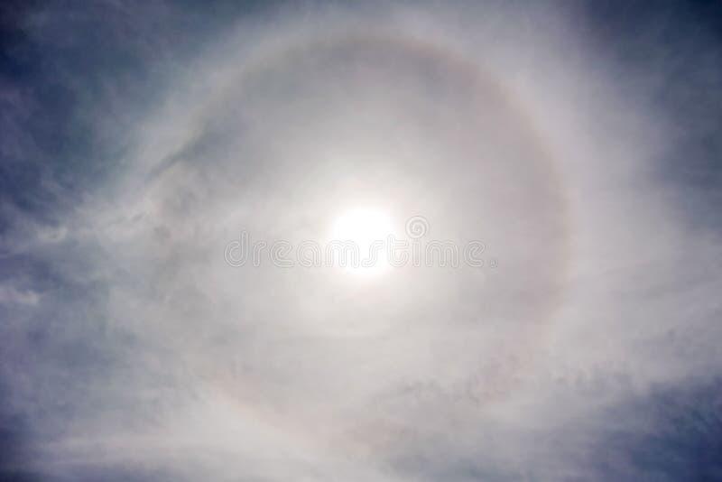 Sun mit dem Kreisregenbogensonnen-Haloauftreten wegen der Eiskristalle in der Atmosphäre, Sonnenhalohintergrund stockfoto