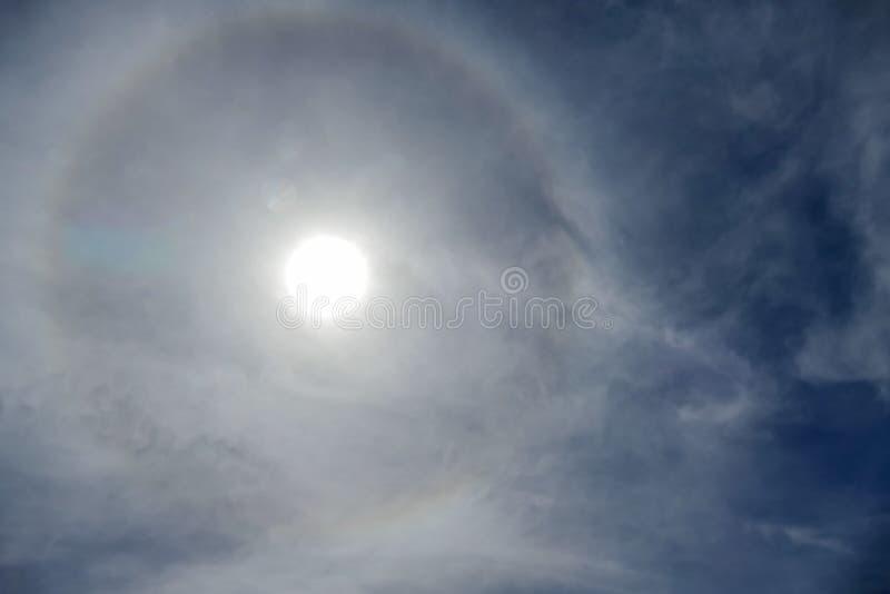 Sun mit dem Kreisregenbogensonnen-Haloauftreten wegen der Eiskristalle in der Atmosphäre, Sonnenhalohintergrund lizenzfreie stockfotos