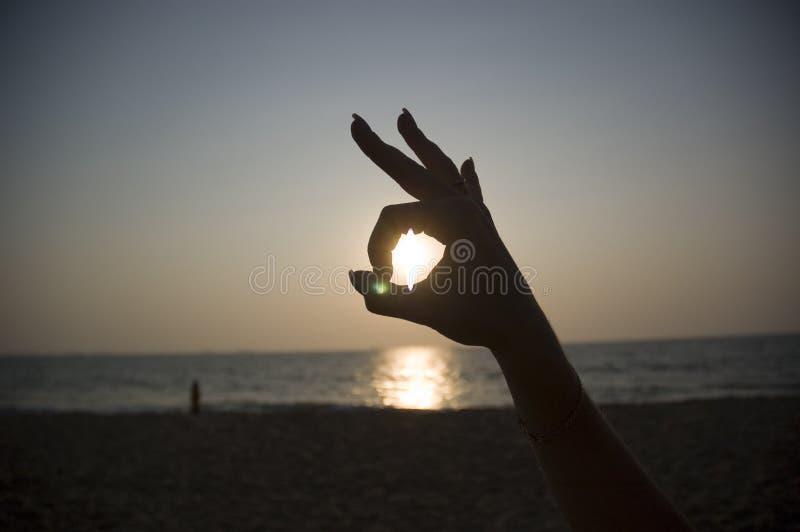 Sun na mão de uma mulher como um sinal da APROVAÇÃO que negligencia o oceano imagens de stock royalty free
