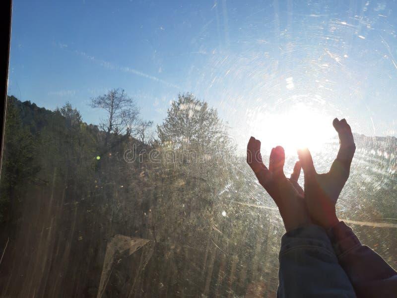 Sun nas mãos fêmeas através do vidro riscado imagens de stock