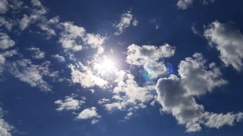 Sun nascosto dietro le nuvole in un cielo blu luminoso immagine stock libera da diritti