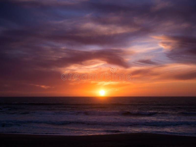 Sun no horizonte no por do sol com o céu alaranjado azul do inclinação e as nuvens dramáticas escuras sobre o oceano imagem de stock royalty free