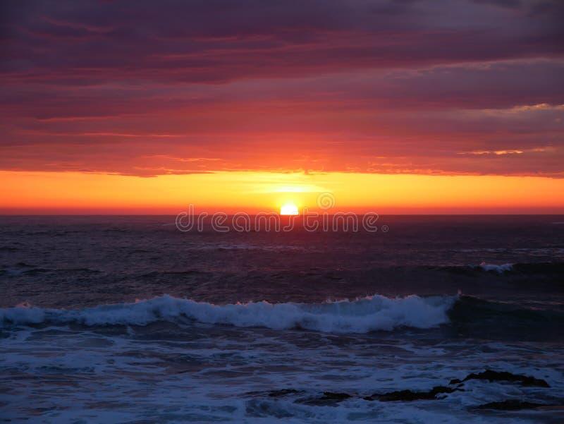 Sun no horizonte no por do sol na praia com o céu alaranjado vívido bonito fotografia de stock