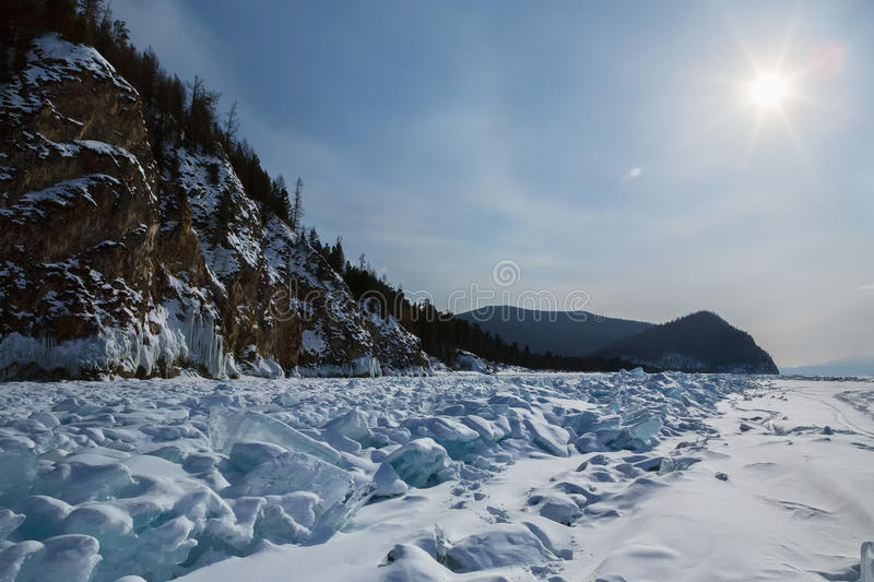 Sun over clumps of blue ice on the snow. Beautiful winter landscape in Lake Baikal. stock image