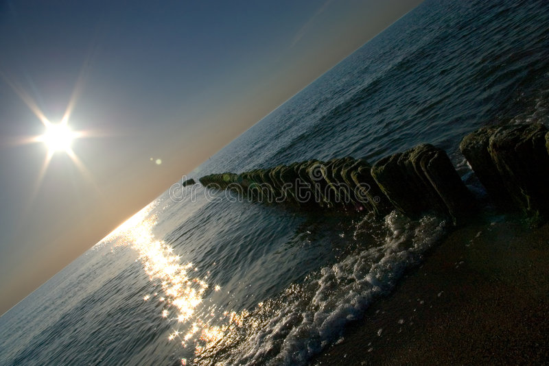 Sun over jetty stock images