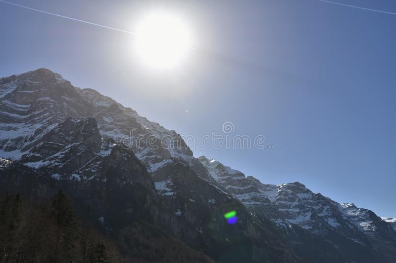Sun over the peak of Alp mountains in the vicinity Klöntalersee lake. Sun over the peak of Alp mountains in the vicinity of Klöntalersee lake in Klöntal royalty free stock photography