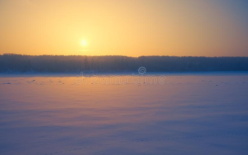 Sun over siberian forest and river Tom under the snow and ice at evening sunset time in winter stock images