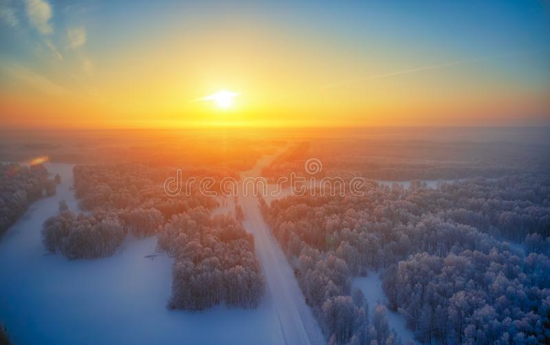 Sun over siberian forest under the snow at morning time. Siberian rural winter sunrise landscape with birch trees covered with stock photos