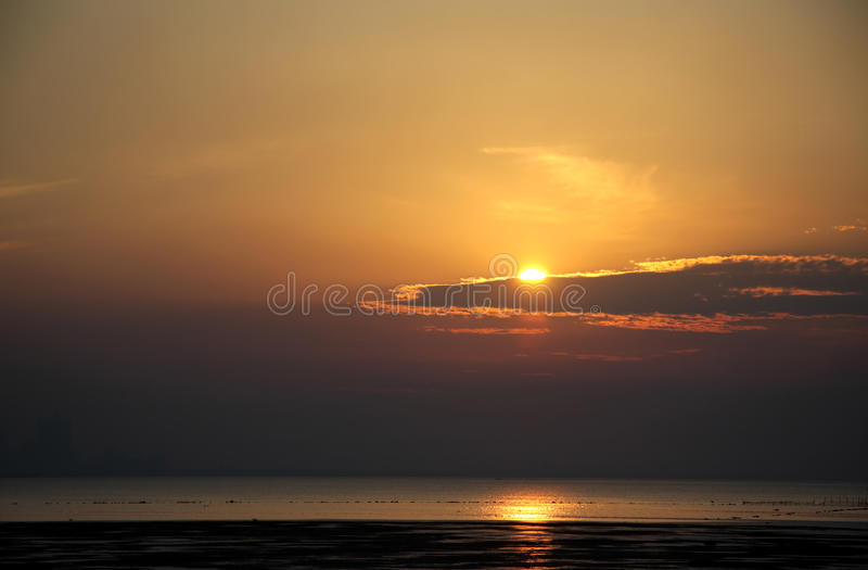 Sun partially covered by cloud at Busaiteen beach royalty free stock photography