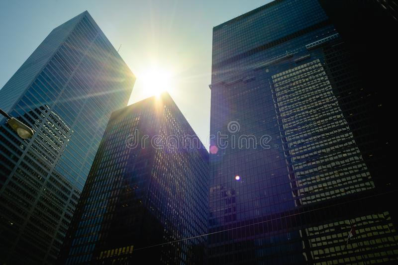 The sun passes between downtown office towers stock photo
