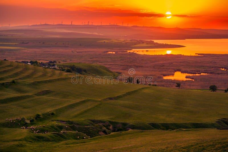 Sun plaçant au-dessus d'un champ des turbines de vent éoliennes et des WI d'une vallée photographie stock libre de droits