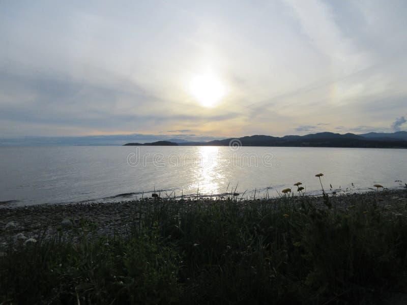 Sun plaçant au-dessus d'une plage rocheuse photo libre de droits