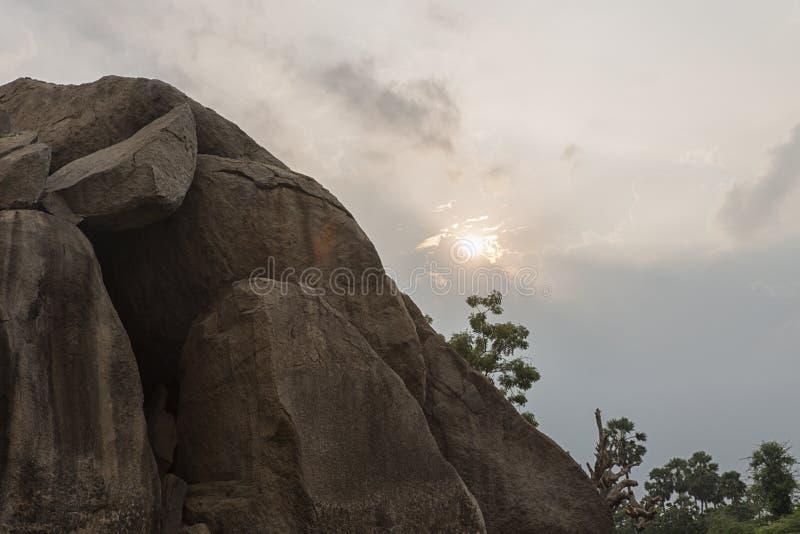 Sun a placé à la boule de beurre du ` s de krishna derrière la roche images libres de droits
