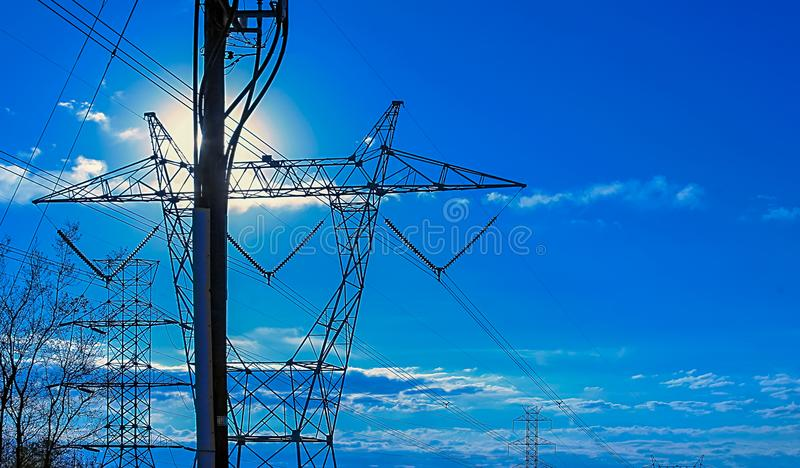 Sun on Power LInes. High power electric towers marching away against a blue sky in the early morning stock photos