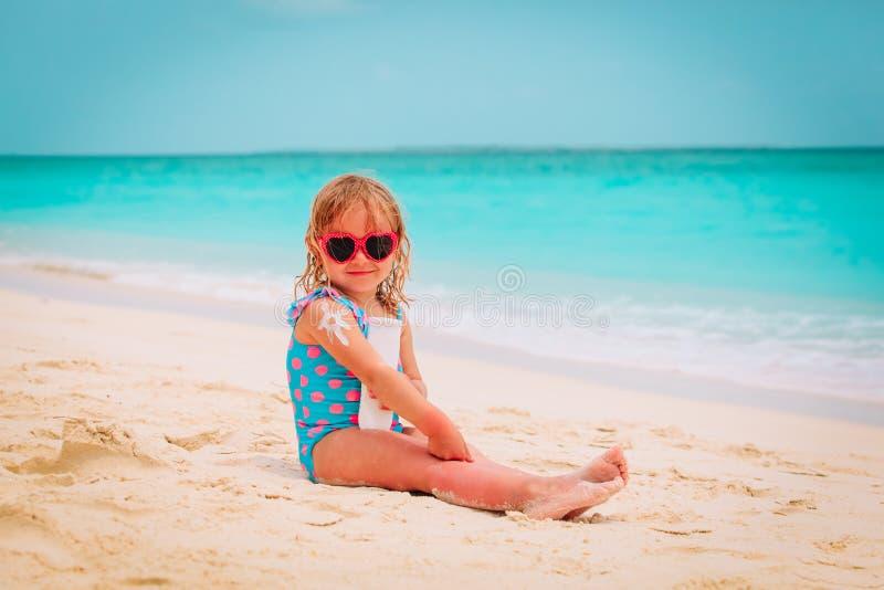 Sun protection on beach- little girl applying sunblock cream on shoulder stock photo