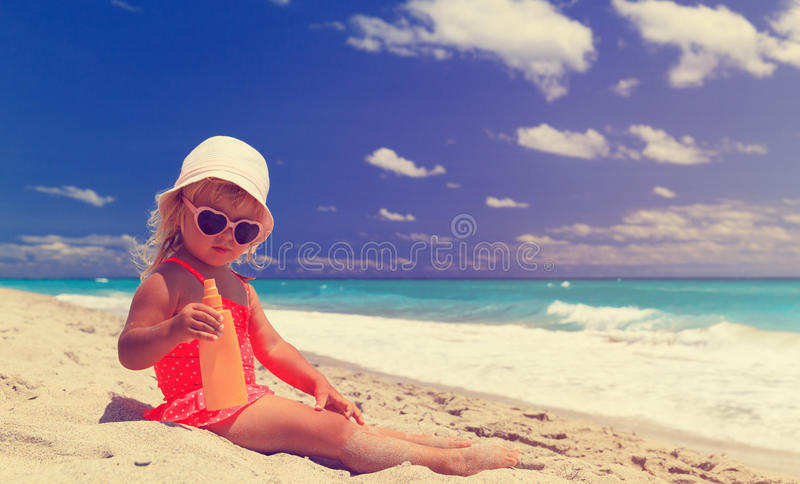 Sun protection concept - little girl with suncream at beach stock images