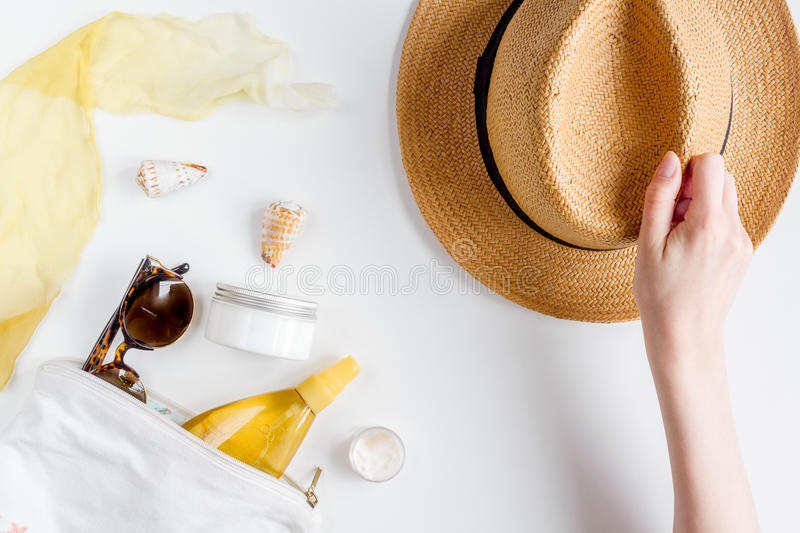 Sun protection cosmetic cream with beach outfit on white background top view. Sun protection cosmetic cream and lotion with beach outfit, sunglasses and hat on royalty free stock photos