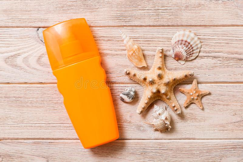 Sun protection cream bottle and seashells on wooden background. flat lay concept of summer travel vacation.  royalty free stock image