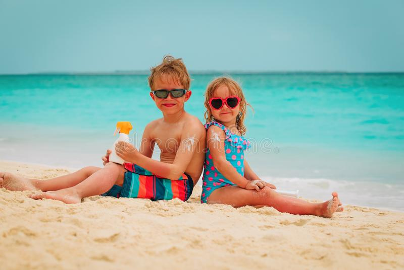 Sun protection- little boy and girl with suncream at beach stock photos