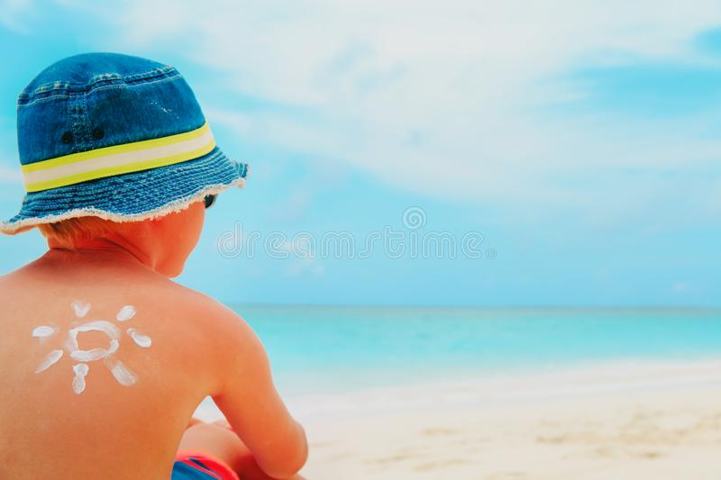 Sun protection- little boy with suncream at tropical beach stock images