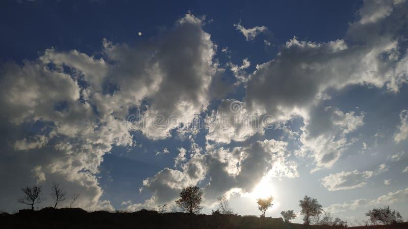 Sun que ajusta-se atrás do monte com árvores imagens de stock